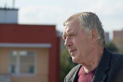 Profil des älteren Mannes nahe bei dem Gebäude Lizenzfreie Stockfotos
