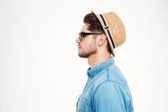 Profil des ernsten Mannes im blauen Hemd, im Hut und in der Sonnenbrille Stockbild