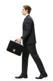 Profil des Gehens mit KofferGeschäftsmann Stockfoto