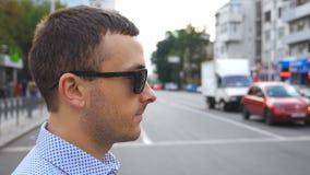 Profil des jungen Geschäftsmannes in der Sonnenbrille, welche die Straße im Stadtzentrum kreuzt Überzeugter männlicher Unternehme stock footage