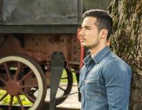Profil des jungen Mannes im Denimhemd nahe altem Zug, gegen Baum Stockfotos
