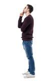 Profil du pull et des lunettes de soleil marron de port de jeune homme imaginant et regardant Photographie stock libre de droits