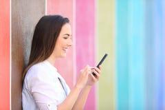 Profil dziewczyna używa mądrze telefon w kolorowej ulicie zdjęcie royalty free