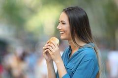 Profil einer Frau, die einen Burger hält stockfoto