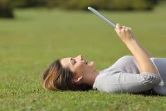 Profil einer glücklichen Frau, die einen Tablettenleser auf dem Gras liest Stockfotos