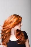 Profil einer kühlen Rothaarigen, die ihr Haar schlägt Stockfotos