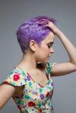 Profil einer kurzhaarigen Frau, die ihr violettes Haar hält Stockfoto