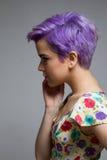 Profil einer violett-kurz-haarigen Frau zuhause, ihr Gesicht halten Stockfotos