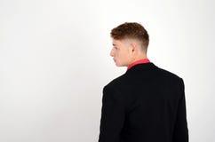 Profil eines jungen Geschäftsmannes, der einen Anzug und ein rotes Hemd schauen zur Seite trägt. Stockfotografie