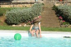 Profil eines Mädchens mit dem Hut, der am Rand des Pools spielt Stockbild