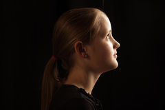 Profil eines Mädchens, welches das Licht betrachtet Stockbild
