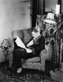 Profil eines Mannes, der in einem Lehnsessel sitzt und ein Buch liest (alle dargestellten Personen sind nicht längeres lebendes u Lizenzfreies Stockbild