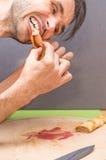 Profil Kaukaski mężczyzna łasowanie staczał się krepę z dżemem na drewnianej tnącej desce Obraz Royalty Free