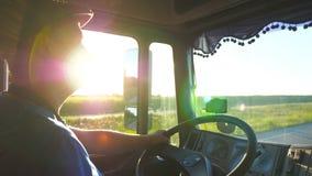 Profil mężczyzna jazda przez wsi z pięknym zmierzchem przy tłem Ciężarówka kierowca kontroluje jego ciężarowego zbiory