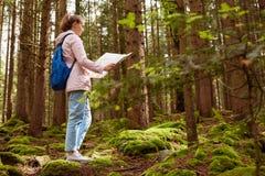 Profil młoda caucasian kobieta z błękitnymi plecakami i mapa dostajemy przegranymi w lesie, wycieczkowiczu patrzeje mapę i próbie fotografia royalty free