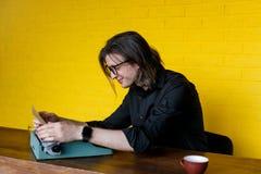 Profil Pocieszny mężczyzna Wkłada Nowego papier W maszynę do pisania W Czarnej odzieży, nad żółtym tłem kosmos kopii zdjęcia stock