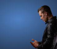 Profil shot from a young man in leatherjacket, rubbing his hand with copyspace Stock Photo
