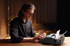 Profil smutny mężczyzna w eyeglass, sadzający przy drewnianym stołem, pracuje na starej rocznik maszynie do pisania w ciemności w zdjęcie royalty free