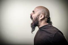 Profil som skriker den ilskna skäggiga mannen Arkivfoto