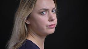 Profil strzelał w średnim wieku blondynka bizneswomanu w błękitnych bluzka zwrotach kamera i zegarki w je na czerni poważnie zdjęcie wideo