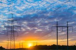 Profila il pilone elettrico ad alta tensione nel fondo del tramonto Immagini Stock