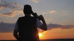 Profila il soldato con l'arma su un tramonto archivi video