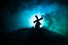 Profila la folla degli zombie affamati e di vecchio mulino a vento sulla collina sul cielo tonificato nebbioso scuro Siluette deg Immagini Stock