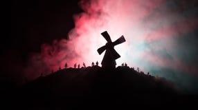 Profila la folla degli zombie affamati e di vecchio mulino a vento sulla collina sul cielo tonificato nebbioso scuro Siluette deg Immagine Stock