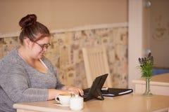 Profilbild av den överviktiga caucasian kvinnan som arbetar i ett kafé royaltyfri foto