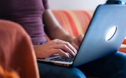 Profildetaljskottet av a mans händer genom att använda en bärbar dator på en soffa arkivbild