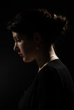 Profile. Side profile of a young woman on a dark background Royalty Free Stock Image
