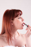Profile. A woman putting on her red lipstick Royalty Free Stock Images