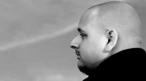 Profile. Bald male, in profile, in front of a lightly cloudy sky stock photos