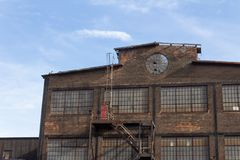 Profile of an abandoned industrial building, circular window in brick facade. Horizontal aspect royalty free stock photo
