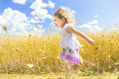 Profile of active running two years old girl at sunny farm rye field summer background Stock Photos