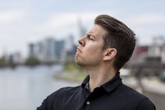Profile of Angry Man With Nose Up in the Air. Profile of an angry man with city skyline in the background Stock Images