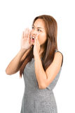 Profile Asian Girl Hands Cupped Around Mouth Away. Profile of lovely Asian girl in gray dress, light brown hair telling secret or shouting announcement looking Stock Image