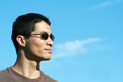 Profile of Asian Man with sunglasses. Blue sky in background Royalty Free Stock Image