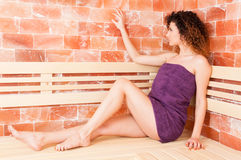 Profile of attractive woman sitting and holding hand on wall Royalty Free Stock Images