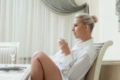 Profile of attractive young blonde drinking coffee Stock Photography