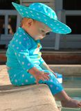 Profile of baby with feet in swimming pool Royalty Free Stock Photo