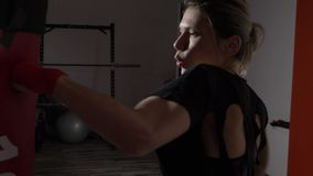 Profile of beautiful attractive blonde woman boxing in a gym to stay fit in slow motion -. Profile of beautiful attractive blonde woman boxing in a gym to stay stock video footage