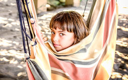 Profile of a beautiful little girl sitting in the hammock on the Royalty Free Stock Photos
