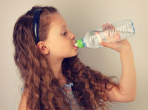 Profile of beautiful long curly hair style smiling kid girl drin Stock Images