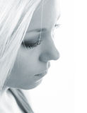 Profile of the beautiful sad girl in blue tones. Profile of the beautiful sad girl with long blond hair isolated on white in blue tones stock images