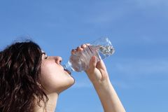Profile of a beautiful woman drinking water from a plastic bottle Royalty Free Stock Image