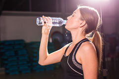 Profile of beautiful woman going to drink some water from plastic bottle after workout.  Royalty Free Stock Photography