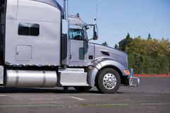 Profile of Big rig gray classic semi truck tractor going to deli. Classic silver gray clean reliable big rig semi truck with high exhaust pipes and chrome Stock Photos
