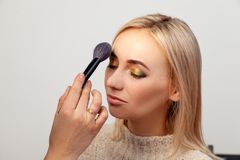 Profile of a blonde model with an oriental-style eye make-up on a white background in the studio, makeup artist with a brush in stock image