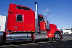 Profile of bright red American big rig semi truck with chrome ac. Profile of bright red big rig classic American semi truck with chrome parts and flat bed semi stock photos